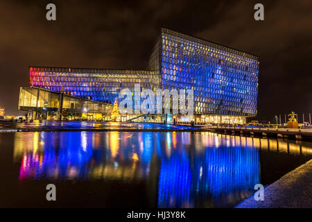 Harpa concert hall in Iceland at night lights up in multiple colors, reflecting on a pool at the front of the building. - Stock Photo