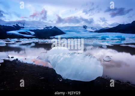 Icebergs along the shore of Jokulsarlon glacial lagoon during a blue overcast day rest motionless while framed by - Stock Photo