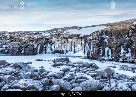 A frozen river in the highlands of Iceland framed by pastel skies and rugged terrain offers scenic landscape epitomizing - Stock Photo