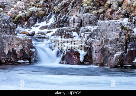 A waterfall surrounded by ice and snow in the highlands of Iceland framed rugged terrain offers scenic landscape - Stock Photo