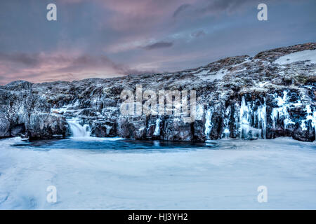 A frozen river in the highlands of Iceland framed by dark pastel skies and rugged terrain offers scenic landscape - Stock Photo
