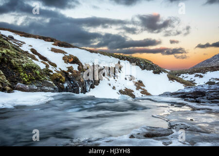 A cold snowy river in the highlands of Iceland framed by pastel skies and rugged terrain offers scenic landscape - Stock Photo