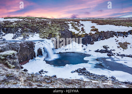 A cold snowy waterfall in the highlands of Iceland framed by pastel skies and rugged terrain offers scenic landscape - Stock Photo