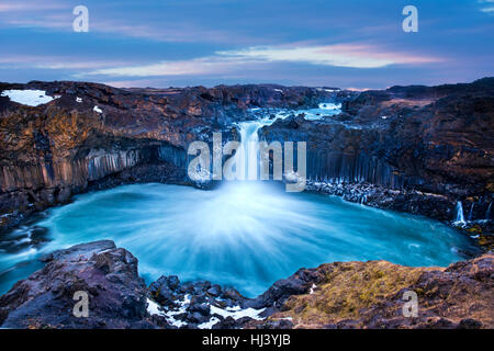 Aldeyjarfoss Falls at Sunrise shows the water pouring over the edge and kicking up a misty cloud over the water. - Stock Photo