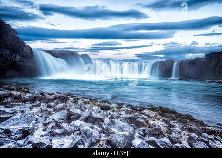 Godafoss Falls during Sunrise shows the water pouring over the edge and kicking up a misty cloud over the water - Stock Photo
