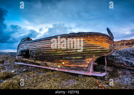 An old abandoned fishing vessel from the early 1900's rests on a remote beach as it rots, exposing the ship's wooden - Stock Photo