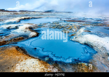 Natural steam rising from volcanic vents in the earth at Hverir in Iceland near Myvatn Lake - Stock Photo