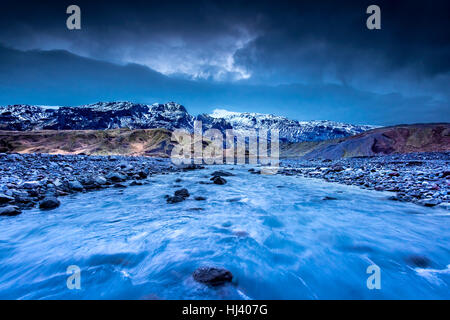 A river formed by melting glaciers flows through a mountain range in northern Iceland during a dark, rainy day. - Stock Photo