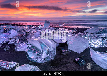 An iceberg along the shore of Jokulsarlon glacial lagoon during a vibrant red sunrise rests motionless as it is - Stock Photo