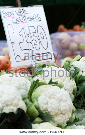 Looking at a market stall with snow white cauliflowers for sale with a tag showing the price, Salisbury, Wiltshire - Stock Photo
