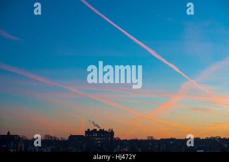 Dawn with a school on the horizon with smoke coming from the chimney - Stock Photo