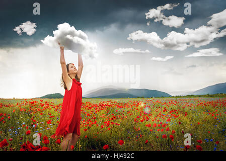 Surreal lifestyle image of young girl in field off poppies catching clouds. - Stock Photo