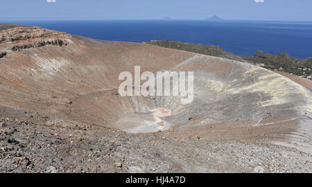 Hiking around the impressive main crater rim of Vulcano Island with Alicudi and Filicudi in the distance - Stock Photo