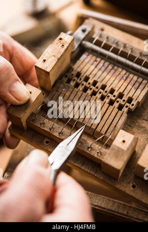 Barrel organ builder, hand bends spring wires made of V2A steel into wooden valves, Grassau, Upper Bavaria, Bavaria, - Stock Photo