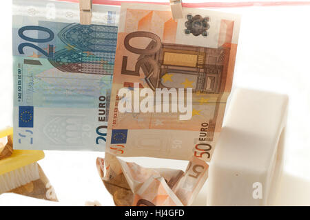 wash dirty money and hang with clothespins - Stock Photo
