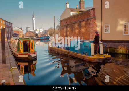 Birmingham Canal Network main line canal, Birmingham city centre with a narrowboat in the middle forground, UK - Stock Photo
