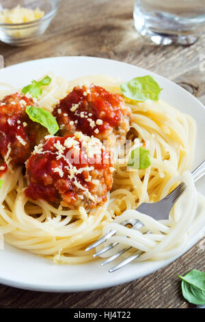 Spaghetti pasta with meatballs, tomato sauce, grated parmesan cheese and fresh basil - healthy homemade italian - Stock Photo