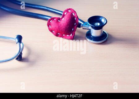 Fabric red heart and stethoscope on wooden table - state on mind, mood or health condition concept, tint image - Stock Photo