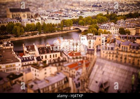 Tilt-shift miniature view across rooftops in Paris toward River Seine - Stock Photo
