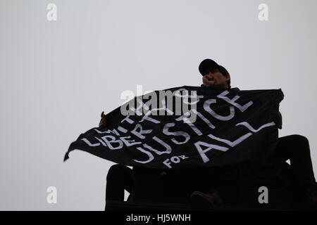 District of Columbia, USA. 21 Jan, 2017. Two men atop a pillar hold a black flag with the words 'WITH LIBERTY & - Stock Photo