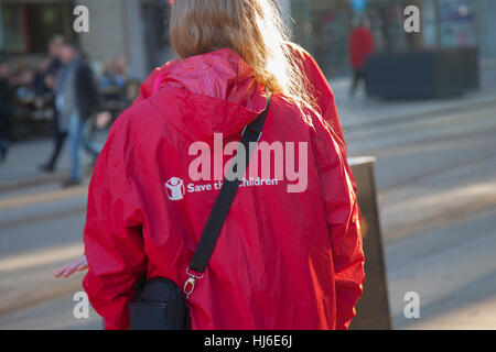 Save the Children Charity worker, canvassing for subscribers in Manchester City Centre, UK  This person approaches - Stock Photo