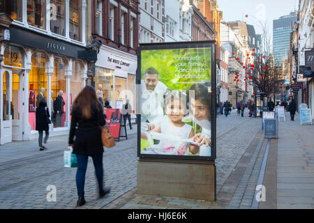 Complete your family by adopting poster on bannerstand. Outdoor Billboard King Street, Manchester City Council Adoption - Stock Photo