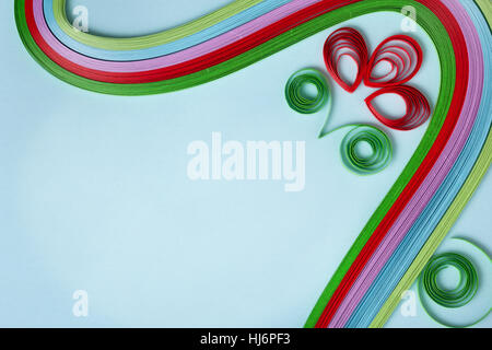 colorful paper quilling closeup on blue cardboard - Stock Photo