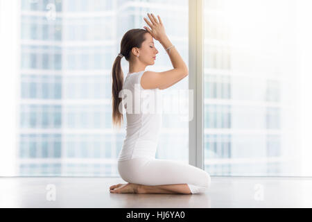 Young attractive woman in vajrasana pose against floor window - Stock Photo