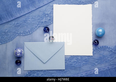 composition of the empty cardboard card and an envelope on fabric background. Flat lay, top view - Stock Photo