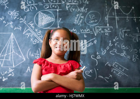 Concepts on blackboard at school. Young people, students and pupils in classroom. Smart hispanic girl writing math - Stock Photo