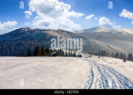 haystack near the path through agricultural field on snowy hillside at foggy morning in winter mountains - Stock Photo
