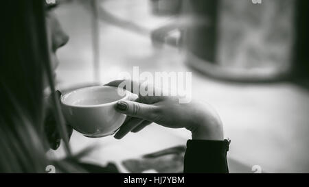 woman behind window in cafe. young girl in black dress sits at table, holding  beverage cup - Stock Photo
