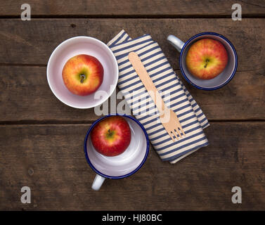 Apples in Bowls with fork and napkin on a rustic wooden table - Stock Photo