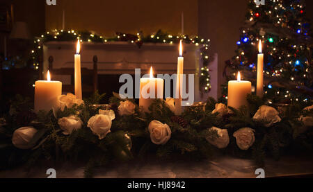 Candles in floral centerpiece on table at Christmas time with a tree in the background - Stock Photo
