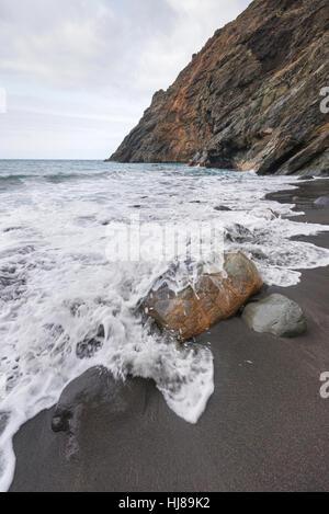 Wave spray splash over the rocky beach on a stormy day in La Gomera, Canary islands, Spain. - Stock Photo