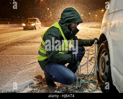 Man with safety vest applying snow chains on snow-covered road, Wattens, Tyrol, Austria - Stock Photo