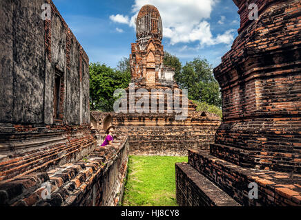 Woman in hat looking at ancient ruined city in Lopburi, Thailand - Stock Photo