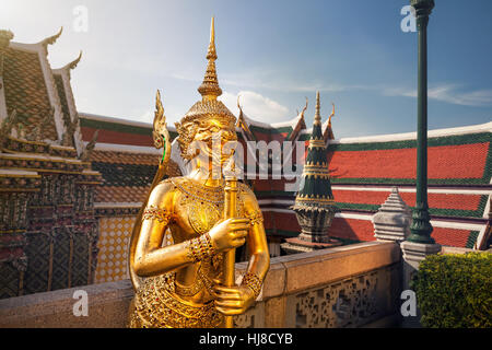 Golden Guardian Statue in the Temple of the Emerald Buddha Wat Phra Kaew in Bangkok at sunset - Stock Photo