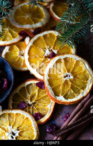 Slices of dried oranges with cinnamon sticks and fir tree branches - Stock Photo