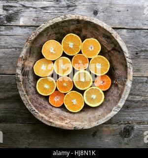 Halved oranges in a wooden bowl - Stock Photo