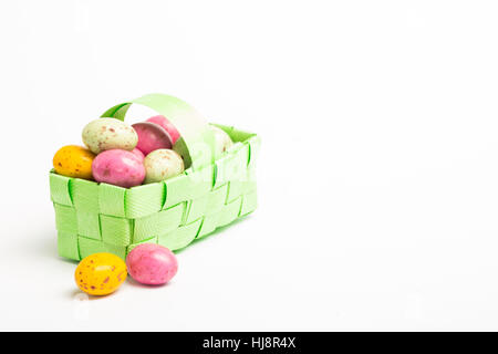 Colourful easter eggs in a green wicker basket on white background - Stock Photo