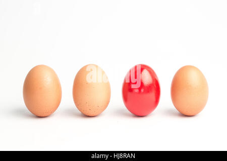 Four eggs in a row with one red one on white background - Stock Photo
