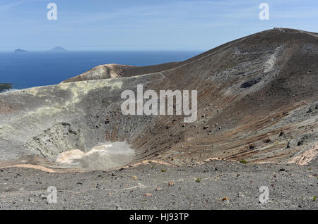 Walking around the Gran Cratere on Vulcano, one of the Aeolian Islands off Sicily, with Panarea and Stromboli in - Stock Photo