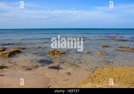 seascape with big textured stone on a foreground in transparent ocean water selective focus Koh Lanta Thailand - Stock Photo