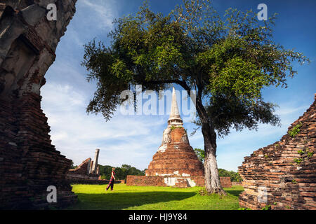 Young woman in red clothes with photo camera looking at ancient ruined Wat Mahathat in Ayutthaya, Thailand - Stock Photo