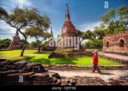 Tourist Woman in red costume looking at ancient ruined stupas in Ayutthaya Historical park, Thailand - Stock Photo