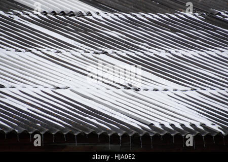A snow covered corrugated metal roof in sections. Icicles hang from the troughs. Located in Siberia, Russian Federation - Stock Photo