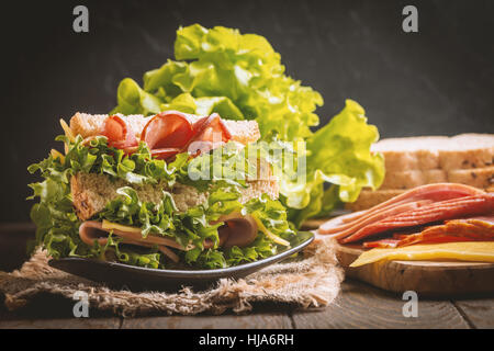 Club sandwich on a rustic table with ingredients - Stock Photo
