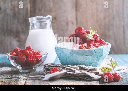 Fresh homemade cottage cheese with juicy raspberries on rustic wooden table, dietary breakfast for summer time - Stock Photo