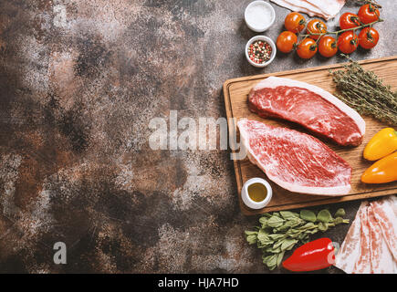 Fresh raw Prime Black Angus beef strip steaks on cutting board over dark rustic concrete background, top view. Ingredients - Stock Photo